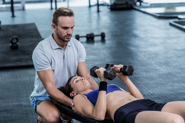 A muscular woman lifting dumbbells