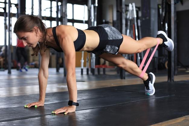 판자 위치에 있는 근육질의 여성은 피트니스 껌을 사용합니다.