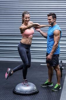 Muscular woman standing on a bosu ball