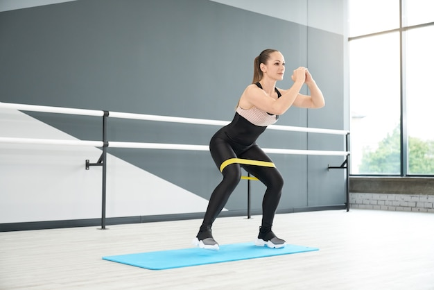 Muscular woman training legs using fitness band