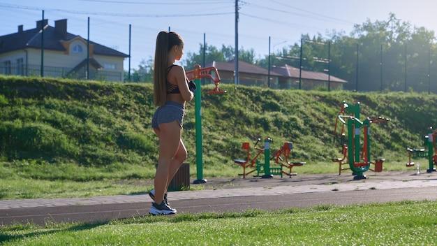 朝のスタジアムで歩く筋肉の女性