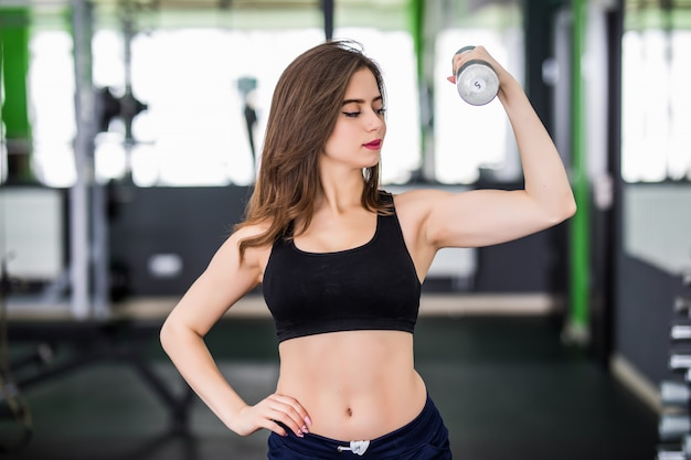 Muscular woman working out in fitness centre with two dumbbells