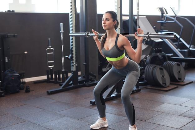 上腕二頭筋でバーベルを使ってエクササイズをしているジムで運動している筋肉の女性。