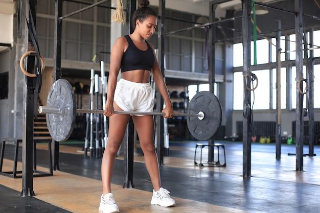 팔뚝에서 바벨로 운동을 하는 체육관에서 운동하는 근육질의 여성.