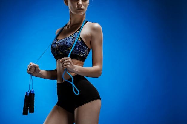 Мускулистый молодой спортсмен со скакалкой на синем