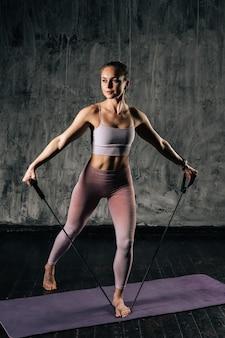 Мускулистая молодая спортивная женщина с красивым телом в спортивной одежде тренируется с группой сопротивления