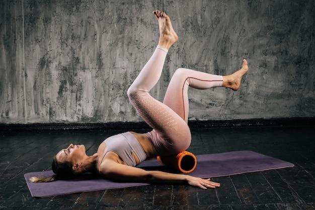 ヨガマットの上に横たわっているフィットネスローラーを使用してエクササイズをしているスポーツウェアの完璧な美しい体を持つ筋肉の若い運動女性。濃い灰色の背景を持つスタジオでポーズをとる白人フィットネス女性。