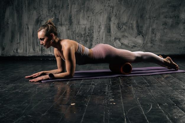 フィットネスローラーを使用し、ヨガマットの上に横たわっている板をやって、脚と腰をマッサージするスポーツウェアの完璧な美しい体を持つ筋肉の若い運動女性。スタジオでポーズをとる白人フィットネス女性。