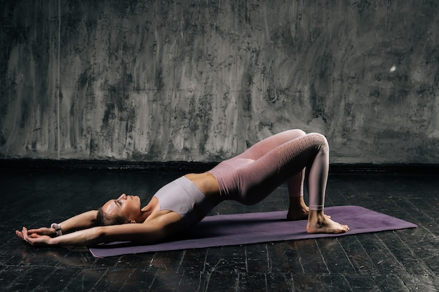 Muscular young athletic woman with perfect beautiful body wearing sportswear doing bridge position lying on yoga mat. caucasian fitness female posing in studio with dark grey background.
