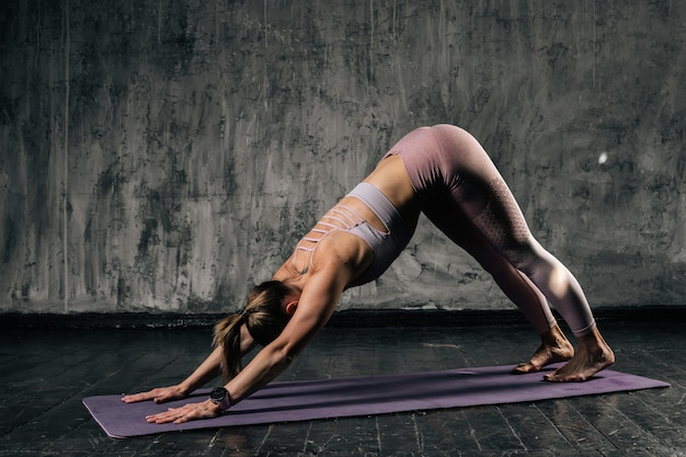 Muscular young athletic woman with perfect beautiful body wearing sportswear doing down facing dog exercise on yoga mat. caucasian fitness female posing in studio with dark grey background.