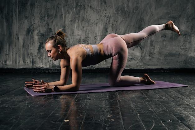 ヨガマットの上でお尻の脚を行使するスポーツウェアを身に着けている完璧な美しい体を持つ筋肉の若い運動女性。濃い灰色の背景を持つスタジオでポーズをとる白人フィットネス女性。