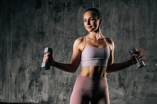 ダンベルで運動するスポーツウェアを身に着けている完璧な美しい体を持つ筋肉の若い運動女性。濃い灰色の背景を持つスタジオでポーズをとる白人フィットネス女性。