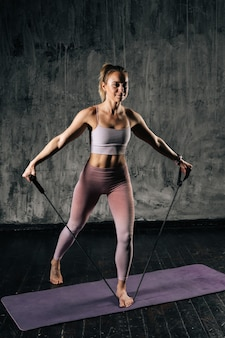 Мускулистая молодая спортивная женщина с совершенным красивым телом, носящая спортивную одежду, тренирующаяся с полосой сопротивления, стоящей на циновке. кавказский фитнес женский тренинг с растягивающим расширителем в студии.