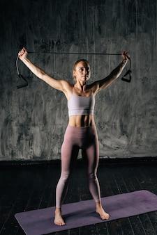 Мускулистая молодая спортивная женщина с совершенным красивым телом в спортивной одежде держит полосу сопротивления над головой, стоя на циновке. кавказский фитнес женский тренинг с растягивающим расширителем в студии.