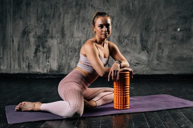 ヨガマットの上にフォームローラーマッサージャーと一緒に座っているスポーツウェアを身に着けている完璧な美しい体を持つ筋肉の若い運動女性。濃い灰色の背景を持つスタジオでポーズをとる白人フィットネス女性。