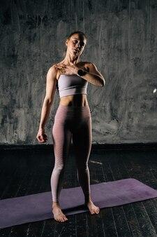마사지 공을 사용하여 운동복을 입고 완벽한 아름다운 몸을 가진 근육질의 젊은 운동 여성