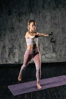 Мускулистая молодая спортивная женщина с идеальным телом, одетая в спортивную тренировку с лентой сопротивления