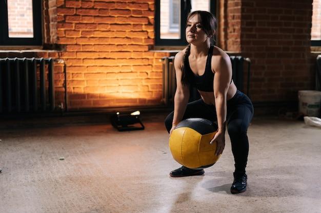 운동 훈련 중에 무거운 메디신 볼과 함께 운동하는 운동복을 입고 강한 아름다운 몸을 가진 근육질의 젊은 운동 여성. 어두운 체육관에서 운동하는 백인 피트니스 여성 운동.