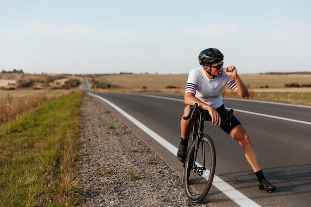 スポーツウェアと黒いヘルメットを身に着けて、道路でリラックスしてスポーツ栄養を食べる筋肉質の若いサイクリスト