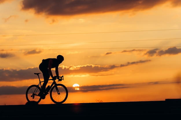 Muscular young cyclist in protective helmet and activewear biking on road during amazing sunset