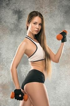 회색 배경에 근육질의 젊은 여성 운동선수. 자신감이 포즈 맞는 몸을 가진 백인 여자입니다. 건강한 생활 방식, 아름다움, 스포츠, 체중 감소 및 다이어트의 개념. 적합. 무게로 연습하십시오.