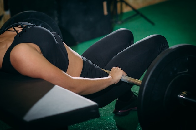 Muscular young fitness beautiful blonde girl lifting a weight cross fit in the gym.
