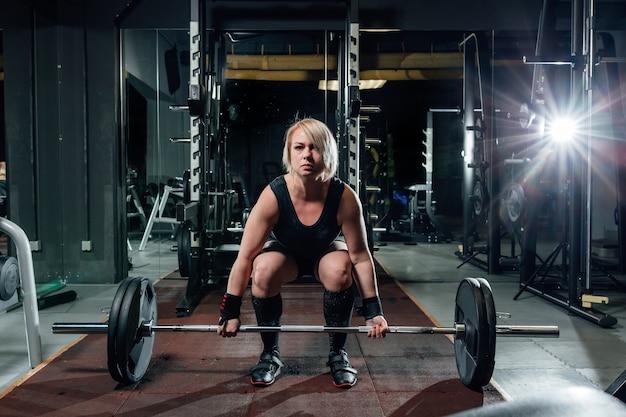 ジムでウェイトクロスフィットを持ち上げる筋肉の若いフィットネス女性。
