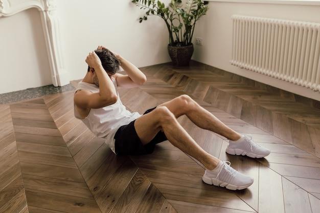 Мускулистый молодой симпатичный белый мужчина тренируется на полу своего дома, тренируя пресс ...