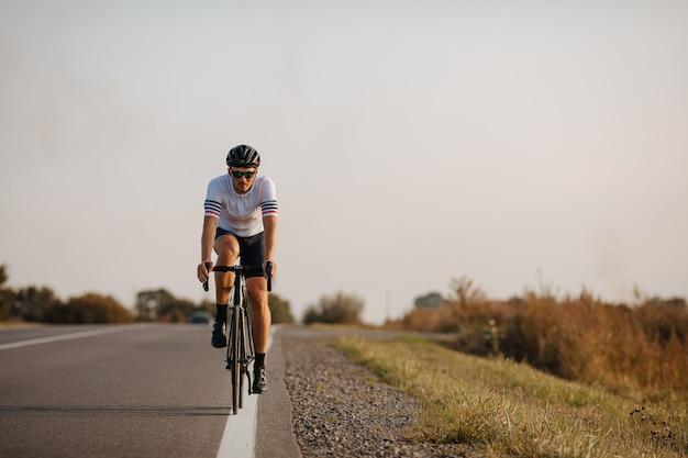보호 헬멧 및 아스팔트 도로의 흰색 라인에 자전거를 타고 안경에 근육 질의 젊은 남자