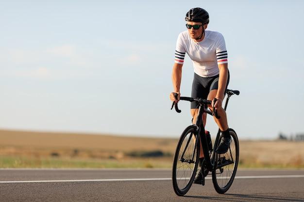 화창한 날 동안 특별한 운동복 승마 자전거에 근육질의 젊은 남자