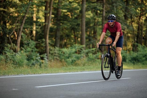 Мускулистый молодой парень в защитном шлеме, зеркальных очках и спортивном костюме едет на черном велосипеде по асфальтированной дороге