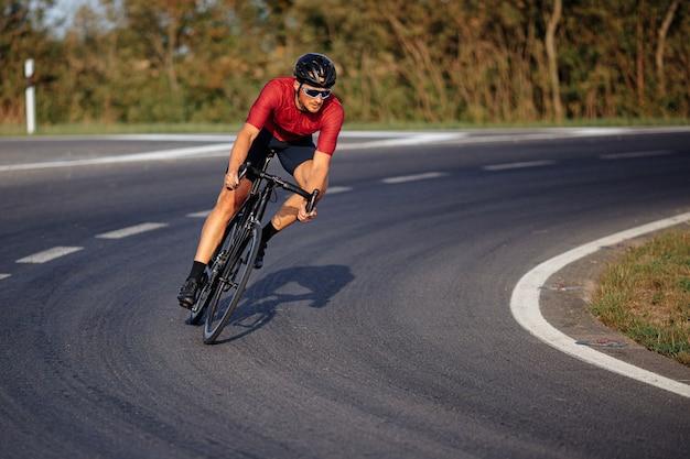 黒の自転車でスポーツ活動を楽しんでいるスポーツ服、保護ヘルメット、ミラーガラスを身に着けている筋肉の若い男