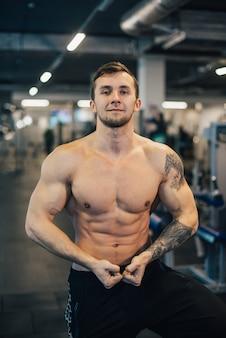 벌 거 벗은 몸통 체육관에 서있는 근육 질의 젊은 남자 선수