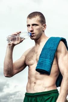 물 한 병을 마시는 운동 후 근육 질의 젊은 남자