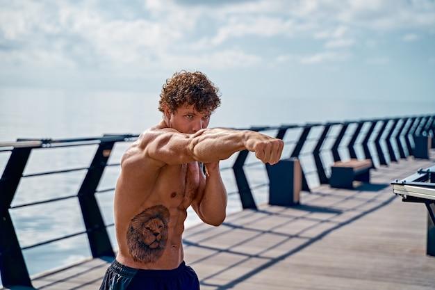 Мускулистый молодой человек-спортсмен, стоящий и практикующий бокс с тенью на открытом воздухе рано утром на пи ...