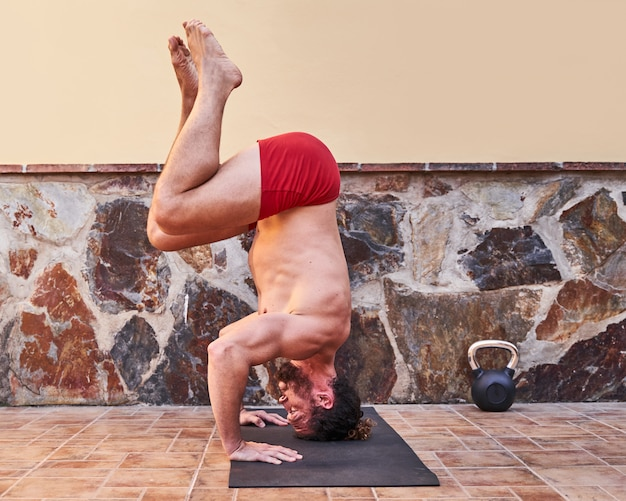 Muscular young man doing handstand at home. home workout concept and healthy living.