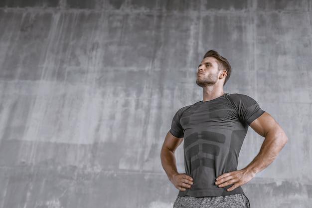 Muscular young man in fashion sportswear on gray wall.
