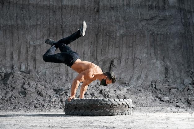 屋外の大きな車輪の手に立っている黒い医療マスクの筋肉の若い男。バランス、持久力、スポーツトレーニングの概念。