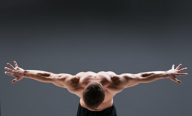 暗い背景のスタジオで筋肉質の若い男は、さまざまな動きと体の部分を示しています。背面図