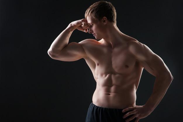 暗い背景のスタジオで筋肉の若い男は、さまざまな動きと体の部分を示しています