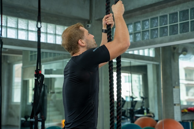 Muscular young man is exercising with battle rope in training fitness gym.