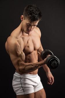 黒い壁にダンベルを持ち上げる筋肉の若い男