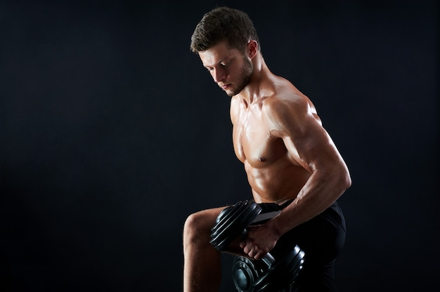 Muscular young man lifting weights on black background