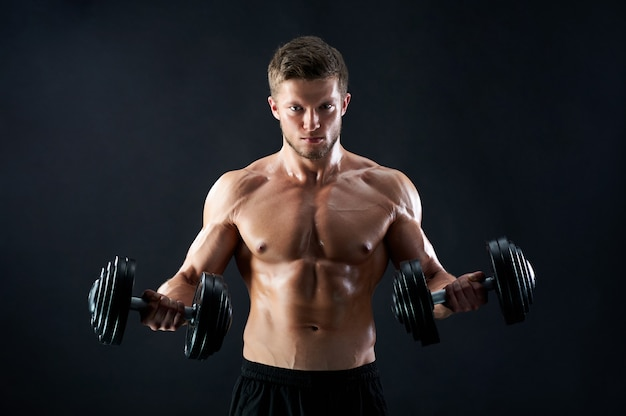 Muscular young man lifting weights on black wall