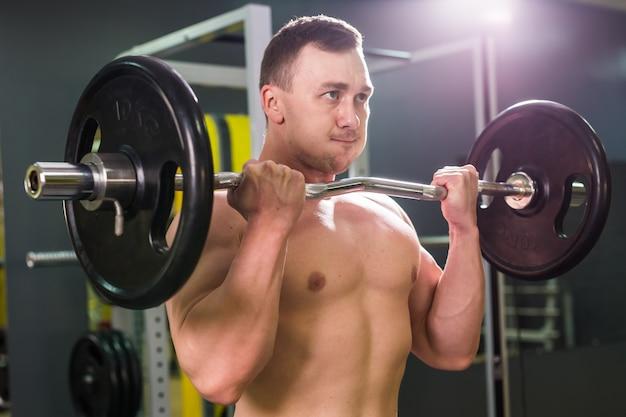 ジムでウェイトリフティング筋肉の若い男。