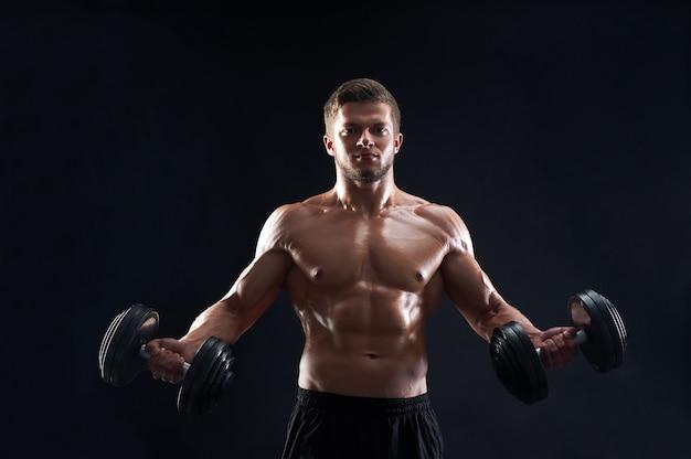Мускулистый молодой человек, поднятие тяжестей на черном фоне