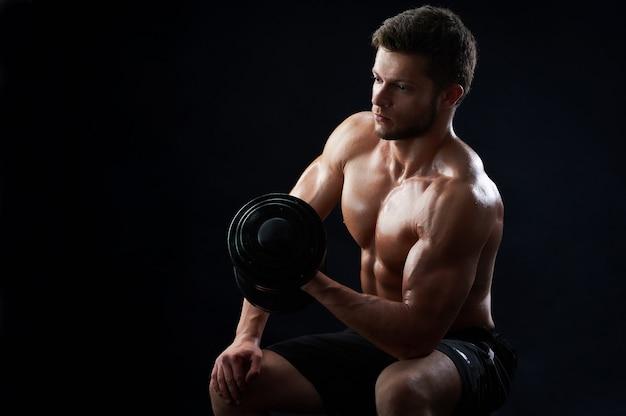 검은 배경에 운동 근육 질의 젊은 남자