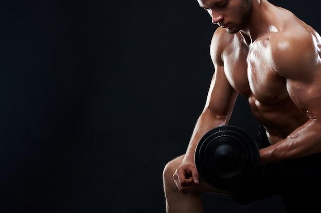 Мускулистый молодой человек, поднимающий тяжести на черном фоне