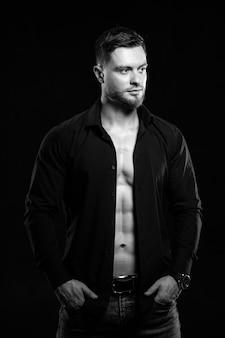 Мускулистый молодой человек на темном фоне в расстегнутой рубашке fark. крупный план. черное и белое.