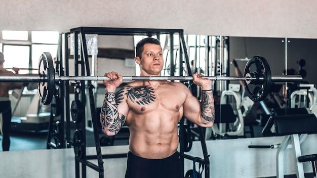 바 벨과 함께 운동을 수행하는 근육 질의 젊은 남자. 스포츠, 헌신, 동기 부여